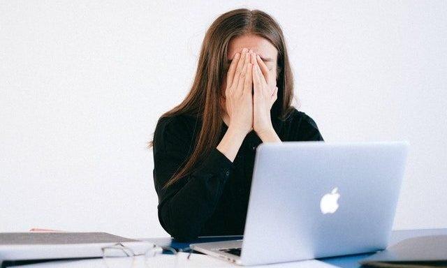 frau ist gestress und unter druck vor dem laptop