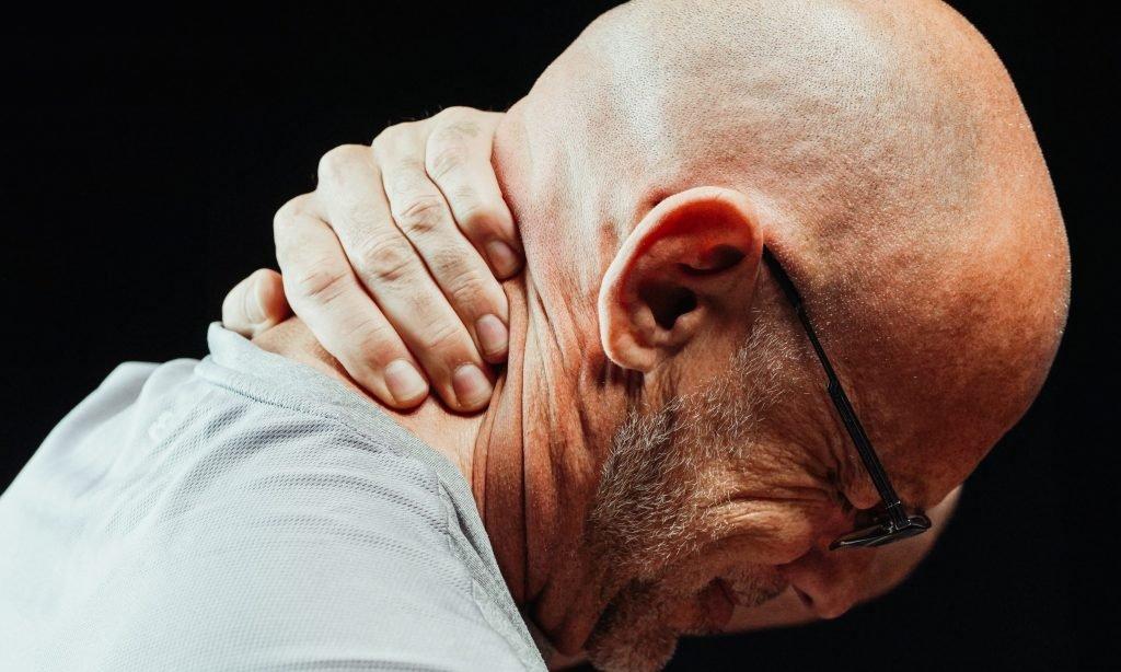 mann hält sich vor schmerzen den nacken